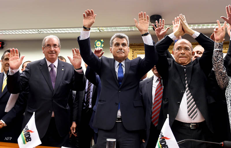 Brazil's PMDB party lawmakers Eduardo Cunha (L), president of the lower chamber, senators Romero Juca (C) and former Civil Aviation Minister  Eliseu Padilha, vote for leaving the government coalition, at the PMDB's headquarters in Brasilia, on March 29, 2016. Brazilian President Dilma Rousseff's ruling coalition collapsed Tuesday when her main partner the PMDB went into opposition, leaving the embattled president increasingly helpless in her fight against impeachment. AFP PHOTO/EVARISTO SA / AFP / EVARISTO SA