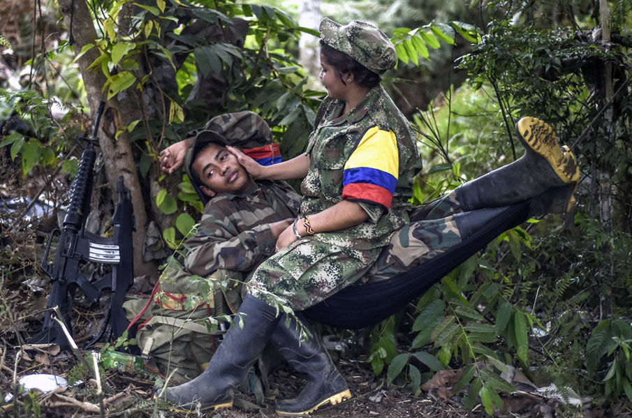 Members of the Revolutionary Armed Forces of Colombia (FARC) take a rest at a camp in the Colombian mountains on February 18, 2016. Many of these women are willing to be reunited with the children they gave birth and then left under protection of relatives or farmers, whenever the peace agreement will put an end to the country's internal conflict.    AFP PHOTO / LUIS ACOSTA / AFP PHOTO / LUIS ACOSTA