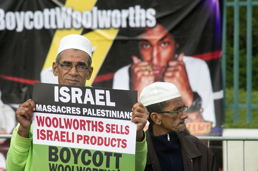 A Muslim man holds a placard reading 'Israel massacres Palestinians. Woolworths sells Israeli products', during a protest against Grammy-winning American musician Pharrell Williams near the Grand west Casino where he was holding a concert in Cape Town, on 21 September, 2015. Supporters of the Boycott, Divestment and Sanctions (BDS) campaign were protesting against the singer's partnership with major South African retail group Woolworths, over its imports from Israel. BDS accuses Woolworths of importing Israeli agricultural produce grown in the occupied Palestinian territories, a charge the company denies. AFP PHOTO / RODGER BOSCH / AFP PHOTO / RODGER BOSCH