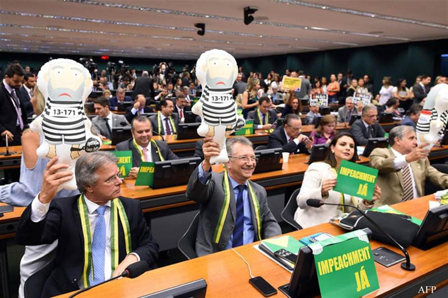 """Opposition deputies hold the inflated dolls of """"Pixuleco"""", representing former President Luiz Inacio Lula da Silva, during the reading of the report by the lower house special committee of impeachment against President Dilma Rousseff, at the National Congress in Brasilia, on April 6, 2016.  The impeachment of Brazilian President Dilma Rousseff should go ahead, the representative for a congressional commission said Wednesday, bringing the country's political crisis a step closer to a showdown. / AFP PHOTO / EVARISTO SA"""
