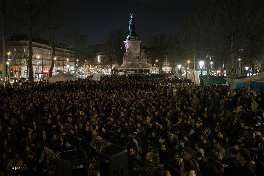 "People listen to speeches as they take part to the ""Nuit Debout"" (""Standing night"") movement in Place de la Republique in Paris on April 5, 2016. Hundreds of people occupy the Place de la Republique every night since March 31, 2016, to protest against the security laws, the poor housing, or labour reforms considered as too liberals. / AFP PHOTO / Elliott VERDIER"