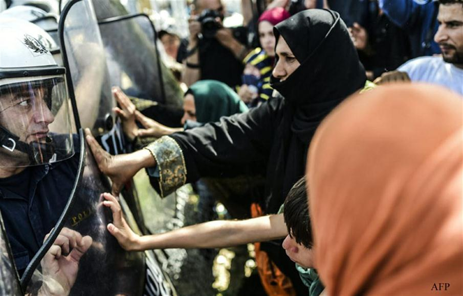 Migrants and refugees clash with riot police during a protest to call for the reopening of the borders at their makeshift camp in the northern border village of Idomeni, on April 7, 2016.  A plan to send back migrants from Greece to Turkey sparked demonstrations by local residents in both countries days before the deal brokered by the European Union is set to be implemented. / AFP PHOTO / BULENT KILIC