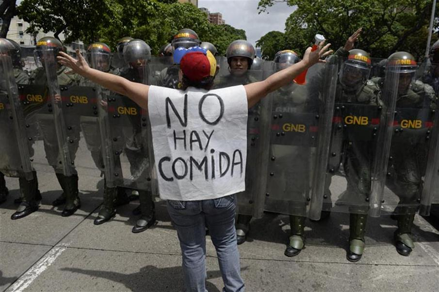 "A woman with a sign reading ""There is no food"" protests against new emergency powers decreed this week by President Nicolas Maduro in front of a line of policemen in Caracas on May 18, 2016.  Public outrage was expected to spill onto the streets of Venezuela Wednesday, with planned nationwide protests marking a new low point in Maduro's unpopular rule. / AFP PHOTO / FEDERICO PARRA"