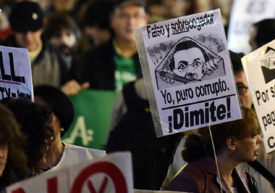 """Demonstrators hold placards during a protest dubbed """" Marches for Dignity"""" (Marchas de la Dignidad) and under the slogan """"Bread, Work, Roof and Dignity"""" against Spanish government imposed austerity measures, in Madrid on October 22, 2015.  AFP PHOTO / JAVIER SORIANO / AFP / JAVIER SORIANO"""