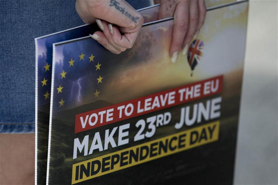 A Leave campaigner holds placards as she waits for the arrival of UK Independence Party (UKIP) leader Nigel Farage in Clacton-on-Sea, eastern England on June 21, 2016. Britain goes to the polls in two days to vote on whether to remain or leave the EU with the result too close to call. / AFP PHOTO / JUSTIN TALLIS