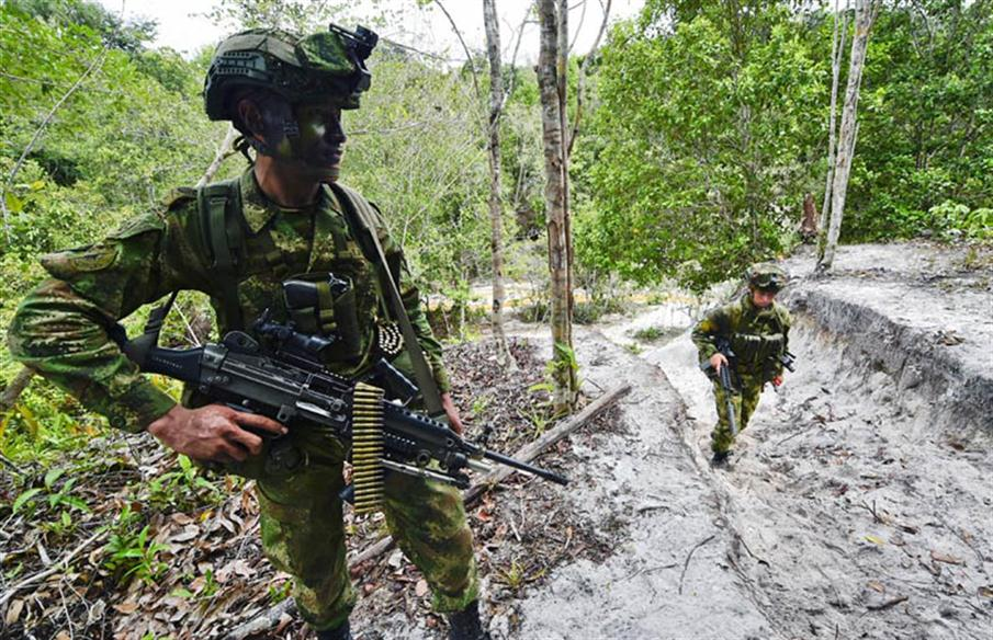 TO GO WITH AFP STORY on illegal mining in Colombia Soldiers patrol the area after taking control of an illegal gold mine during Operation Anostomus, an offensive against illegal mining launched by the Colombian government in the jungles of the departments of Guainia and Vichada, at Puinawai Nature Reserve, Guainia Department, on May 5, 2015. Illegal mining activities take place mostly in areas of environmental conservation as moors, rivers and forests, and produce ecosystem pollution, loss of animals' habitats and displacement of native communities -- areas which are mostly controlled by armed groups, guerrillas and criminal gangs. In Colombia, one of the countries with the largest biodiversity in the world, minerals such as gold, coal, nickel and tungsten are exploited by illegal mining which uses chemical products such as mercury inappropriately, causing pollution in watersheds.   AFP PHOTO / LUIS ACOSTA / AFP PHOTO / LUIS ACOSTA