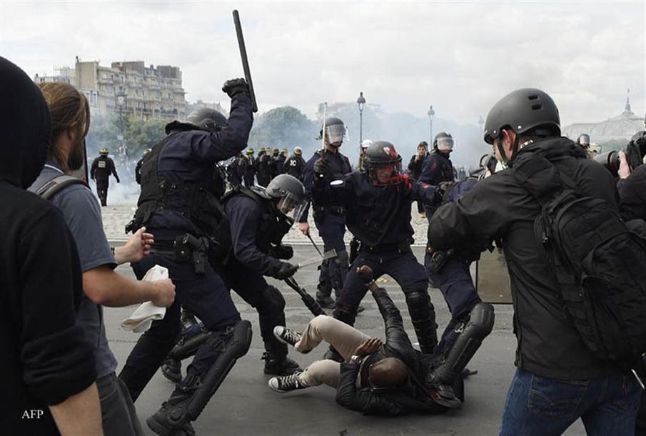 Police officers clash with a demonstrator near the Invalides during a protest against proposed labour reforms in Paris on June 14, 2016.  Strikes closed the Eiffel Tower and disrupted transport in France on June 14 as tens of thousands prepared to march against labour reforms with the Euro 2016 football championship in full swing.  / AFP PHOTO / DOMINIQUE FAGET