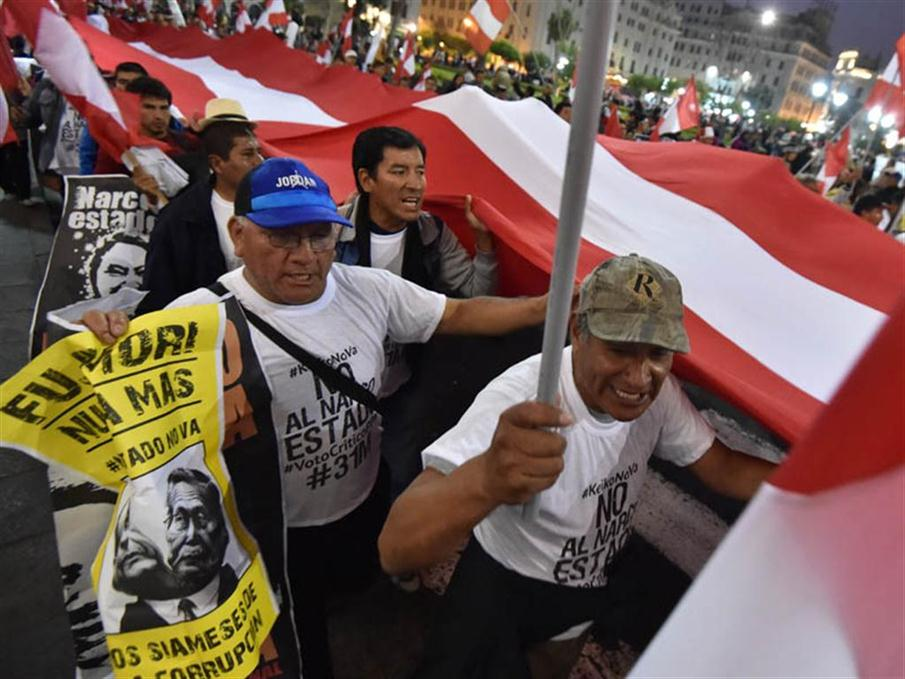 """Thousands of activists gather to rally and march in Lima on May 31, 2016, opposing the candidacy of  Keiko Fujimori, of  the """"Fuerza Popular"""" (Popular Strength) party, to the Peruvian presidency in the upcoming June 5 runoff election. Fujimori, daughter of former President Alberto Fujimori (1990-2000), imprisoned on corruption and crimes against humanity charges, faces Pedro Pablo Kuczynski, candidate of the """"Peruanos por el Kambio"""" (Peruvians for Change) party. Corruption allegations to members of the Fujimori inner circle taint Fujimori's campaign who continues to lead the polls with more than 45 percent of the voting intention. / AFP PHOTO / CRIS BOURONCLE"""