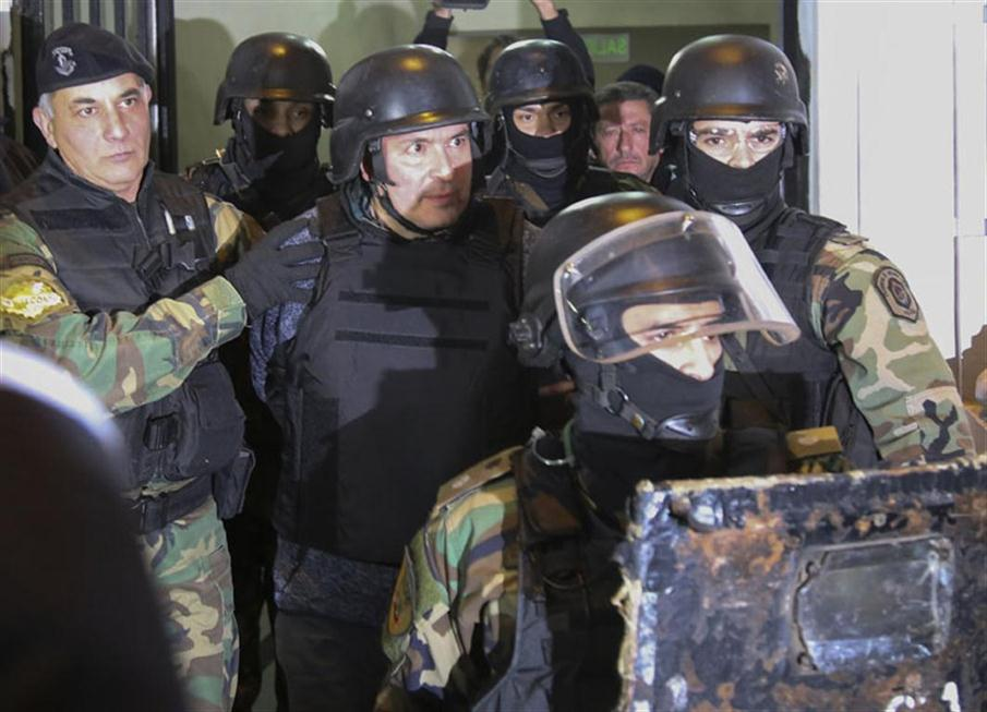 Argentinian former Vice Minister of Public Works (2003-2015) and current Parlasur deputy Jose Lopez (C) is taken into custody after being arrested in General Rodriguez, province of Buenos Aires on June 14, 2016 while he was trying to hide 160 packages with more than eight million dollars in the garden of a nunnery. / AFP PHOTO / Noticias Argentinas / JUAN VARGAS