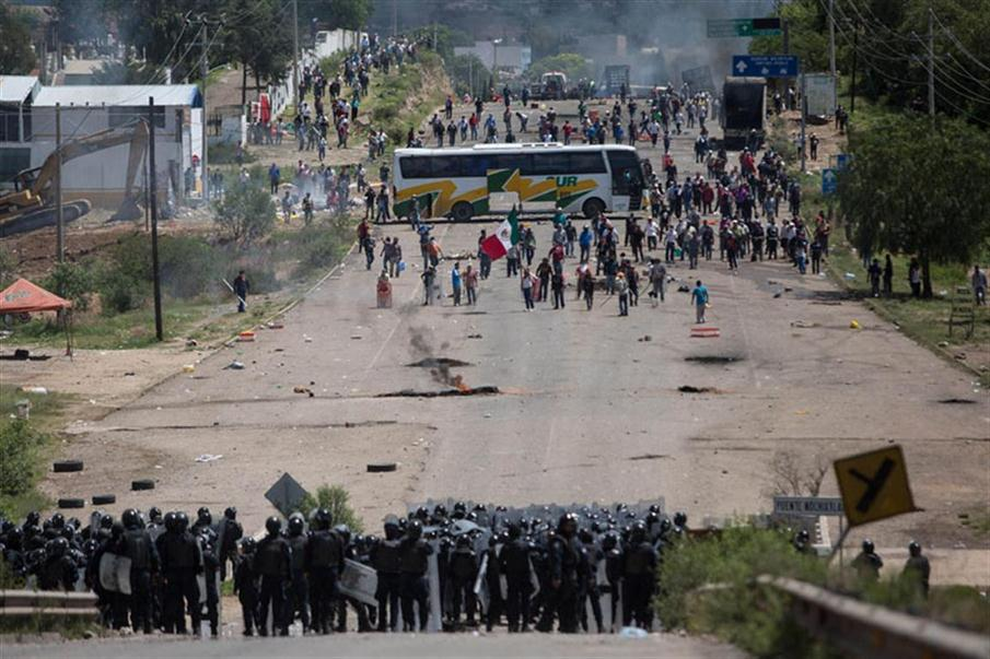 Members of Mexican Federal Police clash with teachers holding a protest against an education reform and the arrest of two of their leaders, in Oaxaca State, on June 19, 2016.  At least three people were killed and dozens injured when police clashed with thousands of teachers blocking roads in a protest in southern Mexico on Sunday, leaving some officers with bullet wounds. / AFP PHOTO / STR