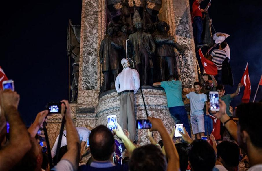 Pro-Erdogan supporters hold an effigy of US-based preacher Fethullah Gulen hunged by a noose during a rally at Taksim square in Istanbul on July 18, 2016 following the military failed coup attempt of July 15. Turkish security forces on July 18 carried out new raids against suspected plotters of the botched coup against the rule of President Recep Tayyip Erdogan, as international concern grew over the scale of the crackdown. Thousands of pro-Erdogan supporters waving Turkish flags filled the main Kizilay Square in Ankara while similar scenes were seen in Taksim Square in Istanbul, AFP photographers said. / AFP PHOTO / OZAN KOSE