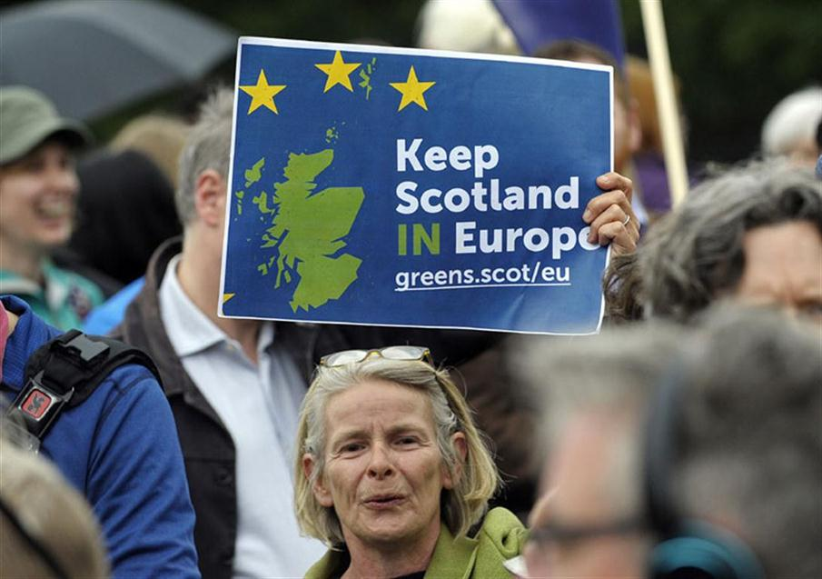 """A woman holds up a placard at a demonstration by Pro EU campaigners outside the Scottish Parliament ahead of a debate on the EU Referendum result and the implications for Scotland, in Edinburgh, Scotland on June 28, 2016. Scottish First Minister Nicola Sturgeon said she would travel to Brussels on Wednesday for talks to defend Scotland's place in the European Union after a vote by Britain as a whole to leave the bloc. Sturgeon said she was """"utterly determined"""" to protect Scotland as she asked an emergency session of the Scottish parliament on Tuesday for a formal mandate for direct talks with the European Union institutions.  / AFP PHOTO / Andy Buchanan"""
