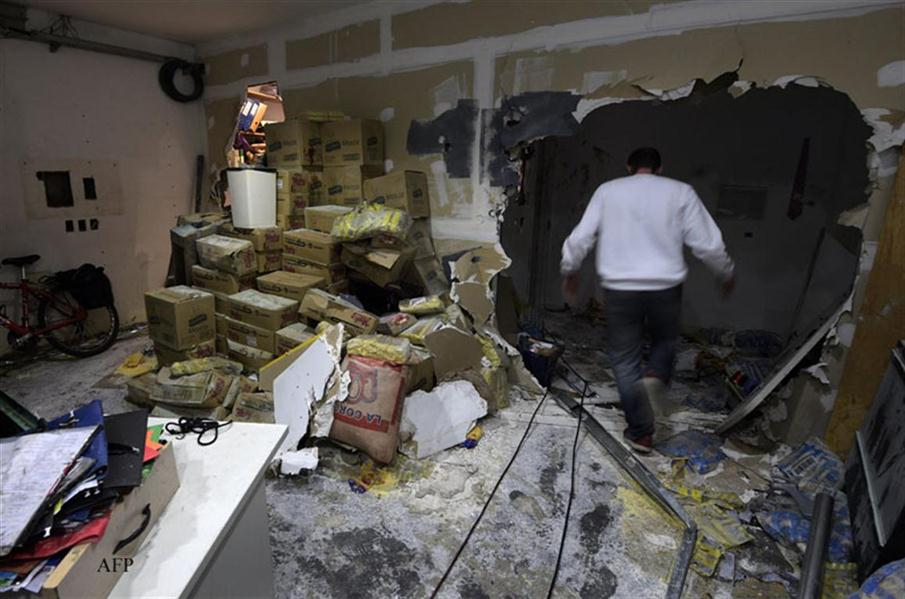 A worker passes through a broken wall at Tiempo Argentino newspaper in Buenos Aires on July 4, 2016. A group of hooded men, among them the alleged new owner of Tiempo Argentino, Mariano Martinez, attacked the offices of the newspaper, destroying everything on their way and assaulting and kicking three journalists present at the moment. The paper's workers kept the publication running after its owners stopped paying salaries in December 2015. / AFP PHOTO / JUAN MABROMATA