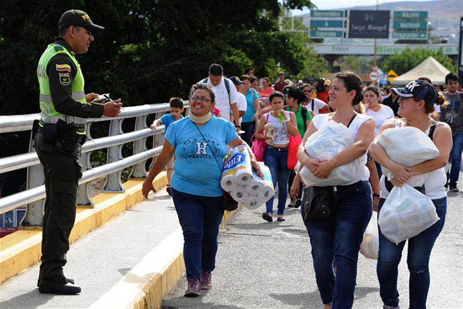 Venezuelans carrying groceries cross the Simon Bolivar bridge from Cucuta in Colombia back to San Antonio de Tachira in Venezuela, on July 10, 2016. Thousands of Venezuelans crossed Sunday the border with Colombia to take advantage of its 12-hour opening after it was closed by the Venezuelan government 11 months ago. Venezuelans rushed to Cucuta to buy food and medicines which are scarce in their country. / AFP PHOTO / GEORGE CASTELLANOS
