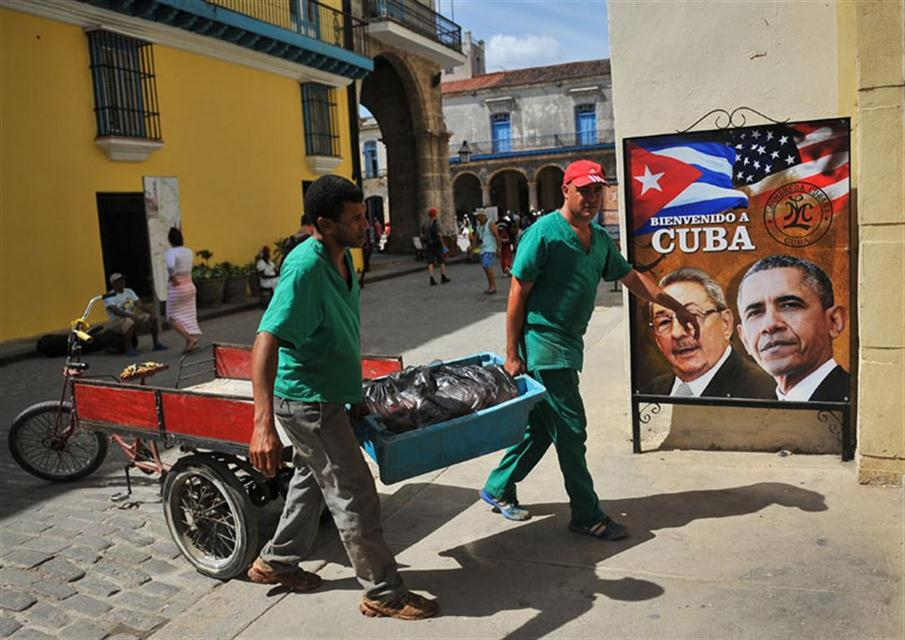 A poster of Cuban president Raul Castro and US president Barack Obama is seen in the entrance of the private restaurant La Moneda Cubana in Havana on March 17, 2016. Hundreds of workers have been scrambling for days to touch up building facades, patch potholes and spiff up Havana's monuments ahead of US President Barack Obama's visit. Obama next week will become the first US president to visit Cuba while in office in almost a century. AFP PHOTO/YAMIL LAGE / AFP PHOTO / YAMIL LAGE