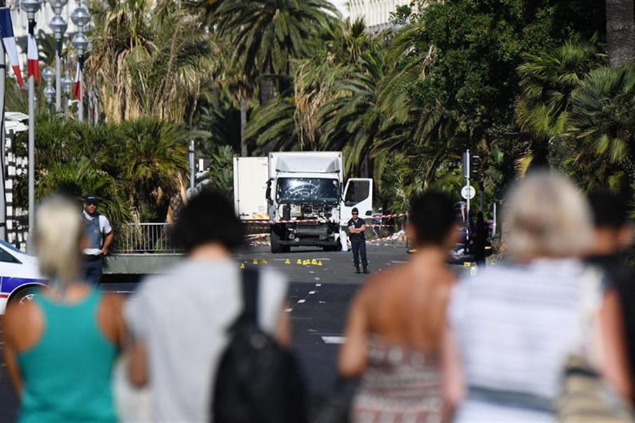 "People look at a truck stand guarded by the police on the Promenade des Anglais seafront in the French Riviera town of Nice on July 15, 2016, hours after it drove into a crowd watching a fireworks display. An attack in Nice where a man rammed a truck into a crowd of people left 84 dead and another 18 in a ""critical condition"", interior ministry spokesman Pierre-Henry Brandet said Friday. An unidentified gunman barrelled the truck two kilometres (1.3 miles) through a crowd that had been enjoying a fireworks display for France's national day before being shot dead by police.  / AFP PHOTO / ANNE-CHRISTINE POUJOULAT"