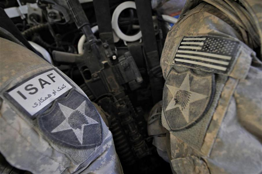 """In this photograph taken October 8, 2009, US Army soldiers from the 5th Stryker Brigade Combat Team, 2nd Infantry Division wear the insignias of their unit bearing a Native American chief and star, together with the ISAF badge and the """"Stars and Stripes"""" US flag on their dusty combat uniforms as they ride on a convoy of Stryker armored vehicle on a mission in southern area of Spinboldak near the Afghanistan and Pakistan border.  The 5th Stryker Brigade is one of the US military units operating under the NATO-led International Security Assistance Force (ISAF). The US has 68,000 forces operating in Afghanistan under the NATO coalition fighting the Taliban insurgency.  AFP PHOTO / ROMEO GACAD / AFP PHOTO / ROMEO GACAD"""