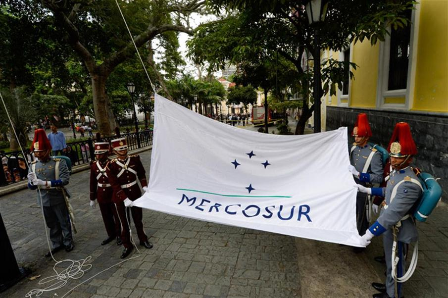 The Mercosur flag is raised in front of the Venezuelan Foreign Office building, in Caracas on August 5, 2016. The act ocurred after a meeting in Montevideo in which the founder members couldn't agree on the leadership transfer. Argentina, Brasil and Paraguay are against Venezuela's leadership of the economic block.  / AFP PHOTO / FEDERICO PARRA