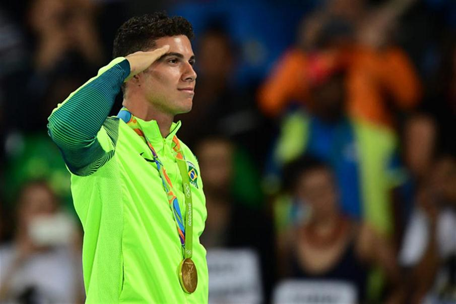 Gold medallist Brazil's Thiago Braz Da Silva celebrates on the podium at the medal ceremony for the men's pole vault during the athletics event at the Rio 2016 Olympic Games at the Olympic Stadium in Rio de Janeiro on August 16, 2016. / AFP PHOTO / FRANCK FIFE