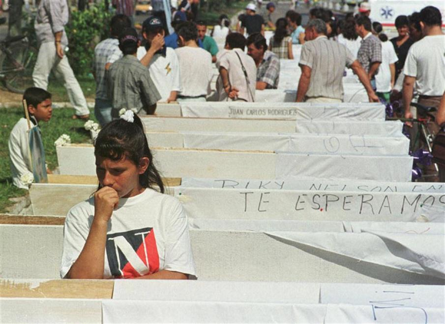 A woman looks at one of the coffins have been put on display to represent 25 people who have disappeared and are believed to have been killed by right-wing death squads 06 June in Barrancabermeja, Colombia. The missing people were rounded up 16 May after being suspected of being leftist sympathizers.   AFP PHOTO/MARCELO SALINAS / AFP PHOTO / MARCELO SALINAS