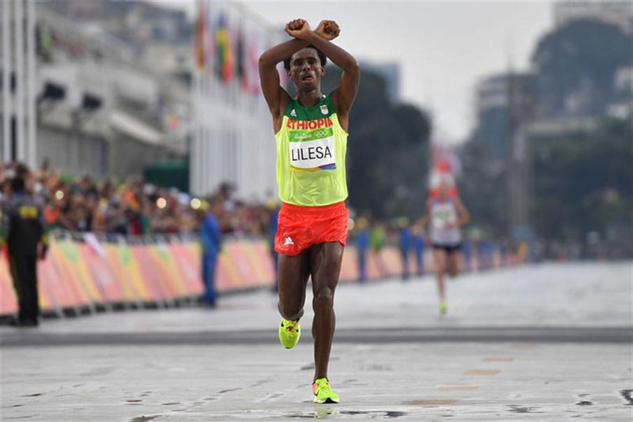 Ethiopia's Feyisa Lilesa (silver) crosses the finish line of the Men's Marathon athletics event at the Rio 2016 Olympic Games at the Sambodromo in Rio de Janeiro on August 21, 2016.   Lilesa crossed his arms above his head as he finished the race as a protest against the Ethiopian government's crackdown on political dissent.  / AFP PHOTO / OLIVIER MORIN