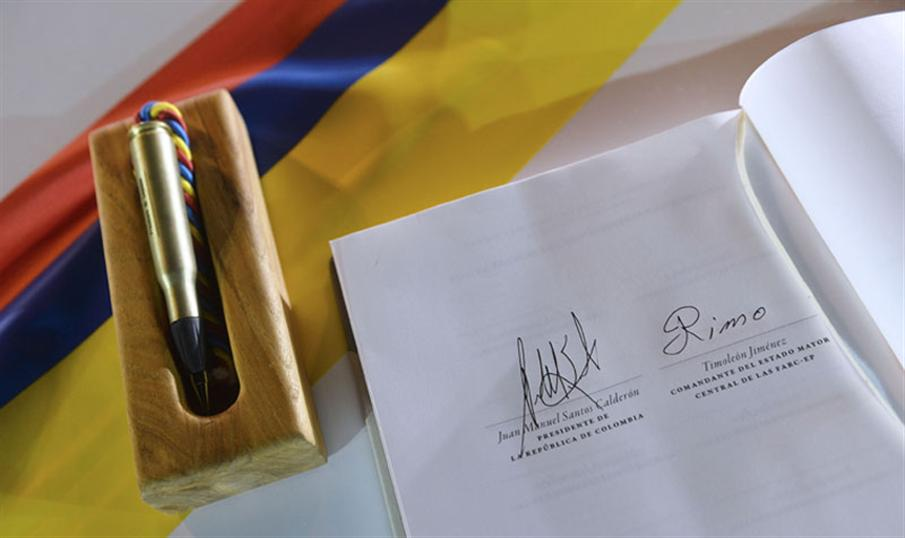 "Handout picture released by the Colombian Presidency showing the document of the peace agreement with the signatures of Colombian President Juan Manuel Santos (R) and of the leader of the FARC, Rodrigo Londono, aka Timoleon ""Timochenko"" Jimenez , in Cartagena, Colombia, on September 26, 2016.  Colombia's leftist FARC rebel force signed a historic peace accord with the government Monday and apologized to the countless victims of the country's half-century civil war. / AFP PHOTO / COLOMBIAN PRESIDENCY / EFRAIN HERRERA / RESTRICTED TO EDITORIAL USE - MANDATORY CREDIT ""AFP PHOTO /PRESIDENCIA/Efrain Herrera"" - NO MARKETING NO ADVERTISING CAMPAIGNS - DISTRIBUTED AS A SERVICE TO CLIENTS"