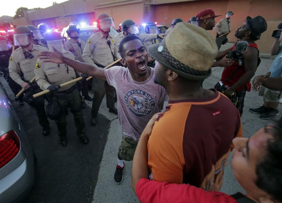 Protesters face off with police, as others try to block them during a rally in El Cajon, a suburb of San Diego, California on September 28, 2016, in response to the police shooting the night before. Protesters marched in a California town following the fatal police shooting of an unarmed black man said to be mentally ill, as local officials urged calm and pledged a full investigation. The victim, identified as Ugandan refugee Alfred Olango, 30, was shot on Tuesday in the San Diego suburb of El Cajon after police received an emergency call about a man behaving erratically and walking in traffic. / AFP PHOTO / Bill Wechter