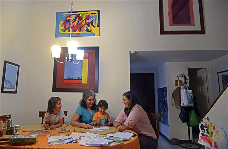 Colombian lesbian couple Ana Elisa Leiderman (L) and Veronica Botero (R) pose with their children Raquel (L), 6, and Ari, 4, both conceived by artificial insemination, at home in Medellin, Antioquia department, Colombia in August 26, 2014. The couple expect the Constitutional Court to rule next Thursday that Veronica Botero be registered also as mother of their children, who grew in Leiderman's uterus and that they both will share their custody. AFP PHOTO/Raul ARBOLEDA / AFP PHOTO / RAUL ARBOLEDA