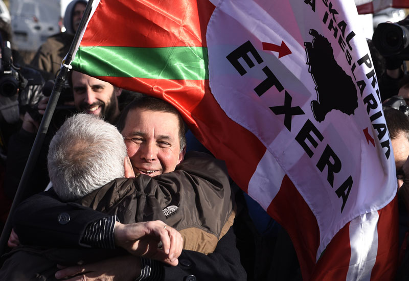 "Leader of the Basque Patriotic Left movement Arnaldo Otegi (R) hugs a friend as he leaves Logrono's prison on March 1, 2016. Arnaldo Otegi was imprisoned since 2009. Banner reads in Basque ""To home"" / AFP PHOTO / ANDER GILLENEA"