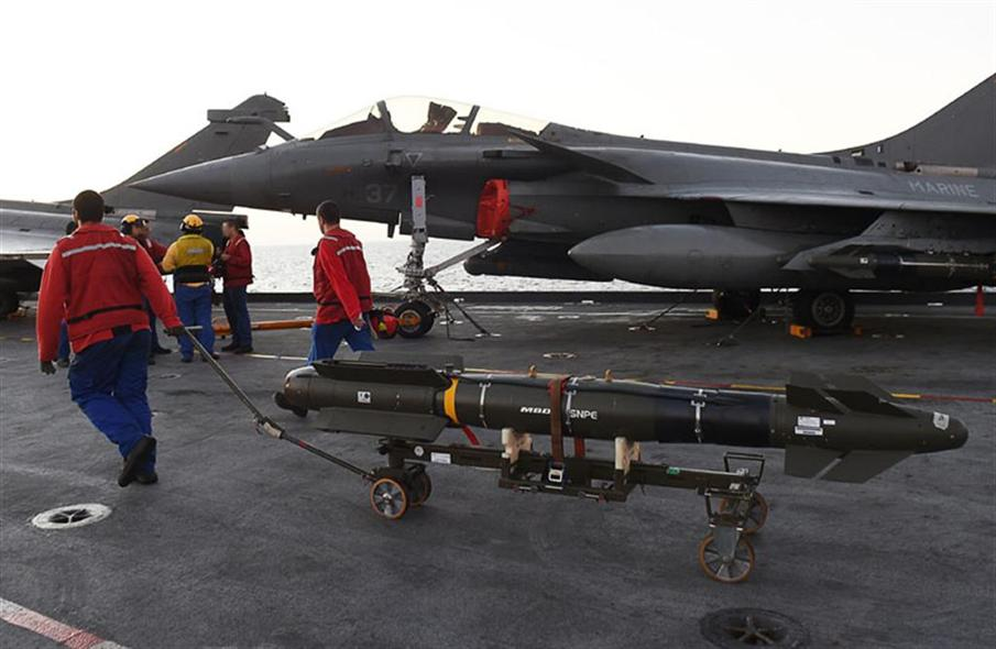 French navy engineers install a missile on a French Rafale fighter aircraft aboard the French Charles-de-Gaulle aircraft carrier, on November 23, 2015 at the eastern Mediterranean sea, as part of operation Chammal in Syria and Irak against the Islamic State group. France launched air strikes against Islamic State group targets in Iraq on November 23 in the first sorties from the Charles de Gaulle aircraft carrier, newly deployed in the eastern Mediterranean. AFP PHOTO / ANNE-CHRISTINE POUJOULAT / AFP PHOTO / ANNE-CHRISTINE POUJOULAT