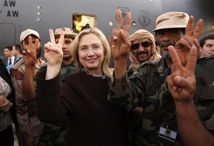 "U.S. Secretary of State Hillary Clinton flashes the ""V"" sign for Victory as she stands along side Libyan fighters loyal to the National Transitional Council upon her departure from  a one day visit toTripoli on October 18, 2011. AFP PHOTO/KEVIN LAMARQUE/POOL / AFP PHOTO / POOL / KEVIN LAMARQUE"