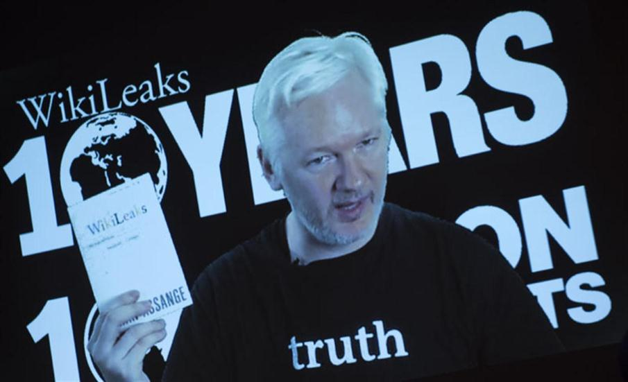 Julian Assange, founder of the online leaking platform WikiLeaks, is seen on a screen as he addresses journalists via a live video connection during a press conference on the platform's 10th anniversary on October 4, 2016 in Berlin. WikiLeaks celebrates its 10th birthday defiantly proud as the pioneer of online leaking platforms, while its controversial founder vows to pursue its work despite widespread criticsm. / AFP PHOTO / STEFFI LOOS