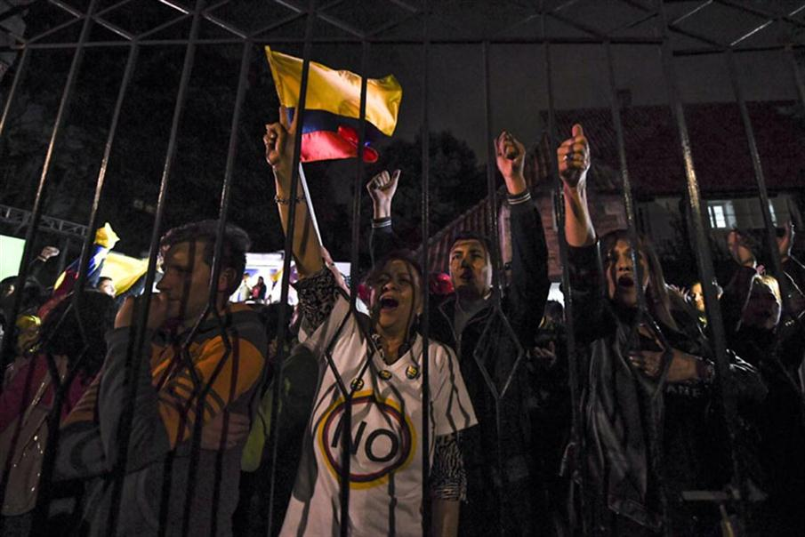 People protest after knowing the results of a referendum on whether to ratify a historic peace accord to end a 52-year war between the state and the communist FARC rebels, in Bogota on October 2, 2016.  Colombian voters rejected a peace deal with communist FARC rebels Sunday, near-complete referendum results indicated, blasting away what the government hoped would be a historic end to a 52-year conflict. / AFP PHOTO / LUIS ACOSTA