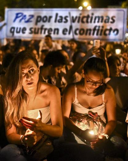 """Demonstrators light candles during a march for the peace in Cali, Colombia, on October 5, 2016. Colombian President Juan Manuel Santos said peace with the FARC rebels is """"close,"""" but his top opponent -- former president Alvaro Uribe -- demanded an overhaul of a """"weak"""" deal rejected by voters in a referendum. / AFP PHOTO / LUIS ROBAYO"""