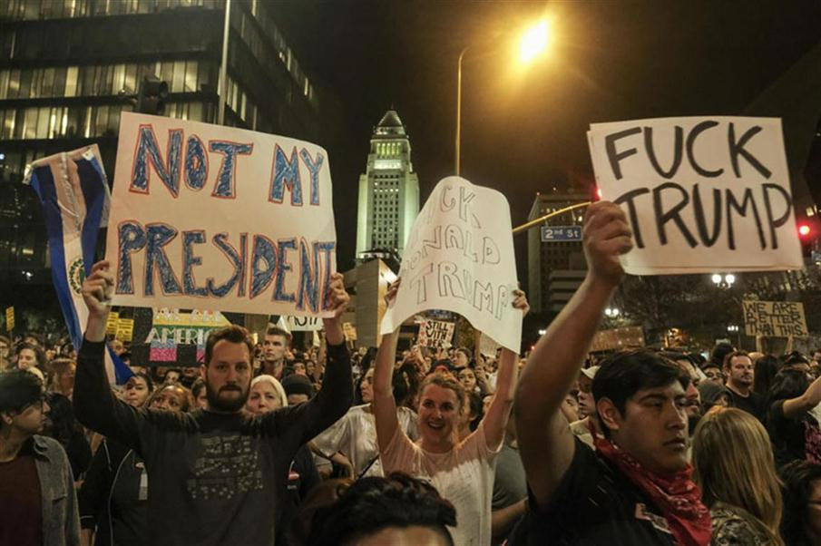 """Demonstrators gather to protest a day after President-elect Donald Trump's victory, at a rally outside Los Angeles City Hall in Los Angeles, California, on November 9, 2016. Protesters burned a giant orange-haired head of Donald Trump in effigy, lit fires ins the streets and blocked traffic lanes late on November 9 as rage over the billionaire's election victory spilled onto the streets of US cities. From New York to Los Angeles, thousands of people in around 10 cities rallied against the president-elect a day after his stunning win, some carrying signs declaiming """"Not our President"""" and """"Love trumps hate."""" / AFP PHOTO / RINGO CHIU"""